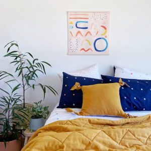 pink wall hanging with fun shapes hanging above bed