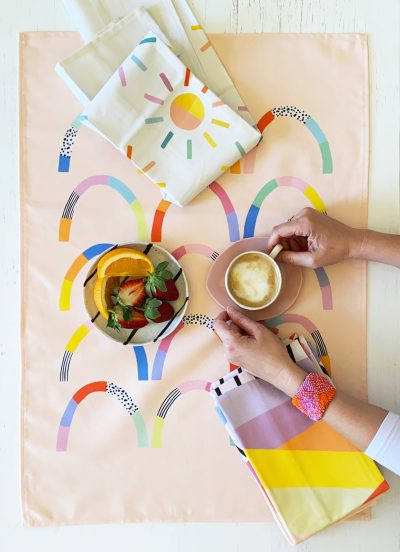 happy hills tea towel flat lay with coffee and fruit